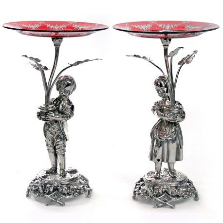 """A beautiful pair of antique Victorian figural boy and girl silver plated comports standing 35.6cm (14"""") tall. The replacement ruby glass and garland engraved dishes and ferns are in plant pots that the figures are carrying. The figures are standing on a cast circular base decorated with cast garlands of flowers on four cast twig effect feet. #victorian #silver #plate #pair #figural #comport #centrepice #boy #girl"""