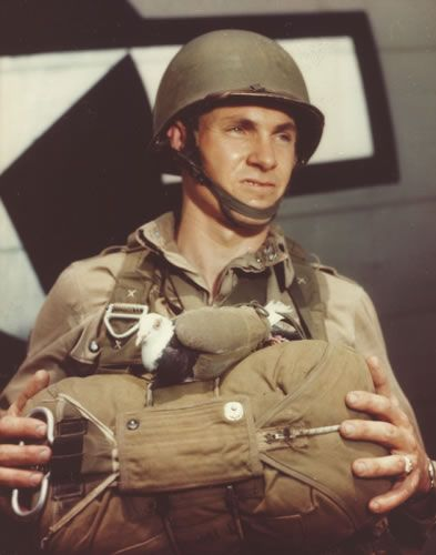 A pigeon in a sling ready for a jump with a US paratrooper (National Archives)