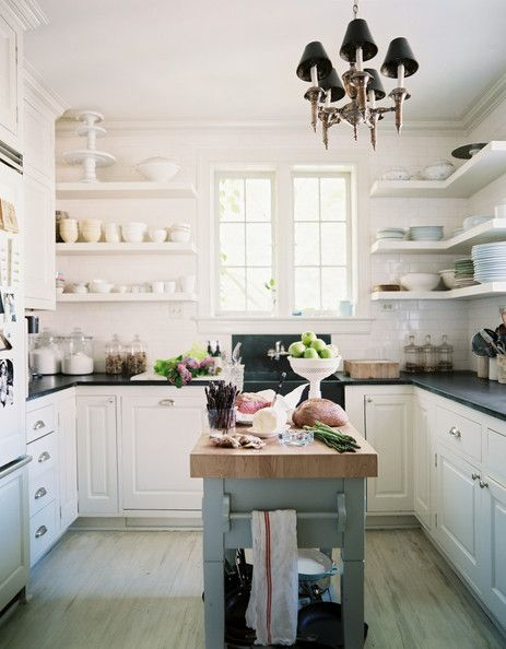 A white kitchen with open shelving and black counter tops