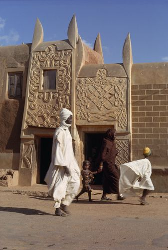 Kano, Nigeria. Hausa architecture. Photo Robert Sisson. 1074389. People walk past sculptured mud walls.