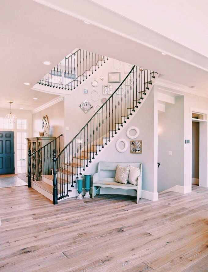 Light Wood Floors And Black Iron Staircase With Light Grey
