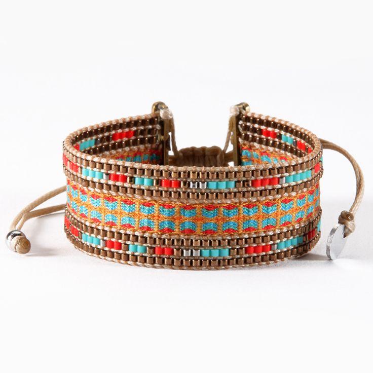 Bracelet Mishky entièrement confectionné à la main avec des perles de verre mordorées, bleues et rouges, et des fils tissés. Fermeture par lien de serrage. Largeur environ 2 cm.