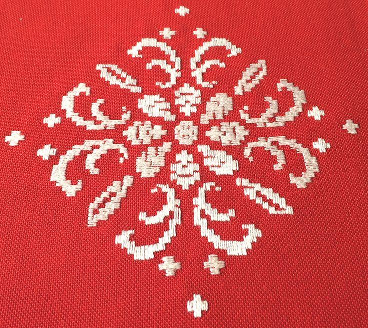 """Mantel de Navidad, de Lagartera, bordado a mano, con un diseño típico navideño.  El diseño representa los clasicos copos de nive del invierno, bordados con la técnica del clásico """"deshilado"""" o filtiré y punteado en blanco, sobre tela de color roja, combinando con otros copos bordados totalmente en blanco.  Estos manteles tan tradicionales quedan fenomenal con una vajilla moderna y completan la mesa de forma espectacular. Podrás comprar este mantel en www.lagarterana.com"""