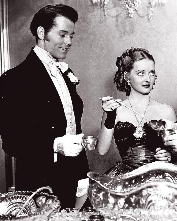 "A still of Jezebel [Bette Davis} with her one-time beau, Henry Fonda to her right. Davis is looking left where another [unseen] co-star, George Brent, is standing having his cup filled. Jezebel was crafted for Davis as a kind of consolation prize for not getting the part of Scarlett O'Hara. Davis certainly made the most of the opportunity. The Oscar and the movie definitively made her a ""star."""
