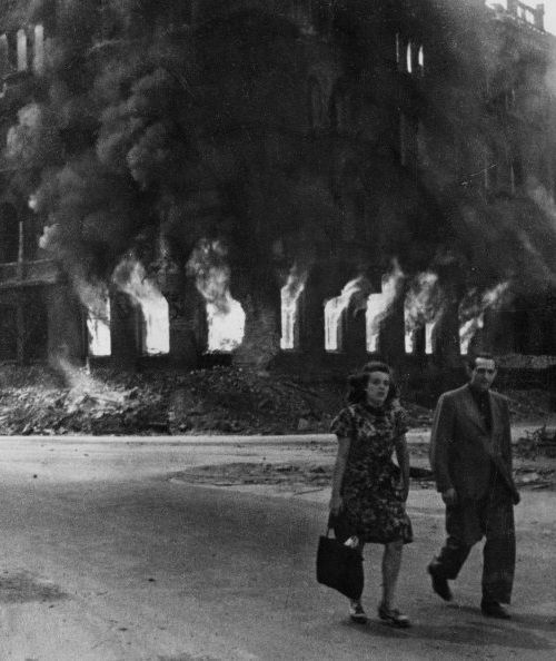 A couple walks through the burning streets of Berlin in the final days of the war, 1945. DHM