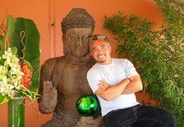 Cesar Millan standing next to a statue