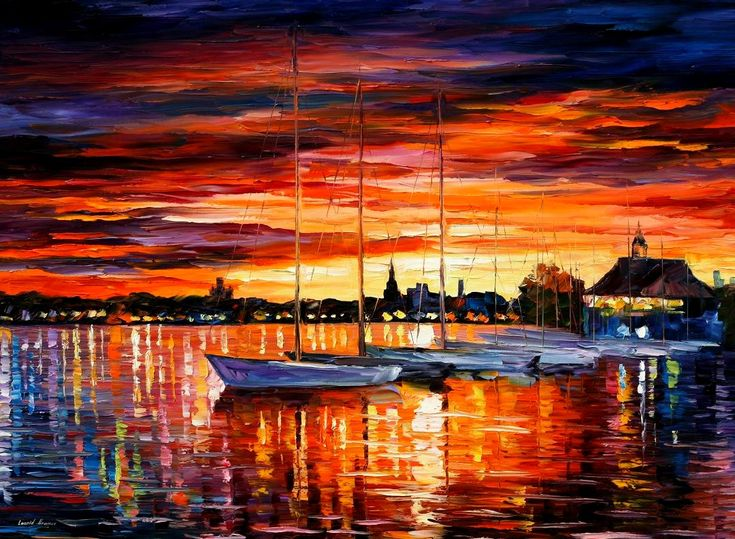 The gorgeous blues and fiery orange reds of the sunset are reflected beautifully in the watery surface behind the empty-masted boats, as their sailors join together in the club onshore to enjoy the co