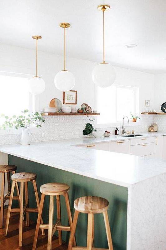 Modern kitchen design ideas. White kitchen with green counter and brass pendants.