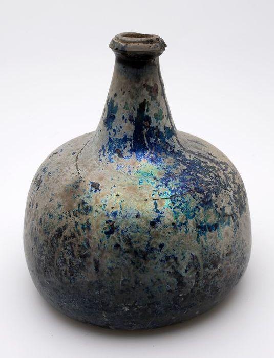 Rondbuikige fles in helder groen glas. Pontilmerk onder opgestoken (4,0 cm, dm 8,5 cm) bodem. Lichaam met vrijwel verticaal opgaande wand naar bolle schouders en verjongde (dm 5,0 - 2,4 cm) hals met opgelegde rondom gaande scherpe glasdraad (waarvan helft afgebroken) en afgeplatte lip (chip). Blauwgroene irisatie.