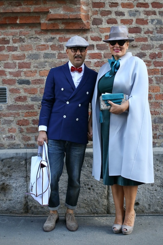 Our 25 Favorite Street Style Snaps from Milan Fashion Week: This duo just looks so dapper together! We love the hats, and her cape is pretty fantastic. (IMAXtree)