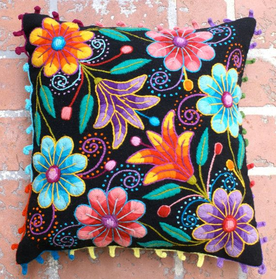 Vibrant, colorfull flowers pop beautifully from the black background of this hand embroidered cushion. Fantastic textures of needlework from the Andes to your home. The pilllows are first woven on a traditional loom with sheep wool and later adorned with hand embroidered flowers made of alpaca wool. A playful crochet trim gives this cushions the perfect finish.  Back zipper clousure. Measures 16 in x 16 in 1 pillow covers included . No inserts or fillers included  Please note that color…