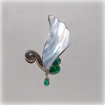 Mother of pearl swan brooch with emerald colored crystals and handmade sterling silver details. Made in our shop.