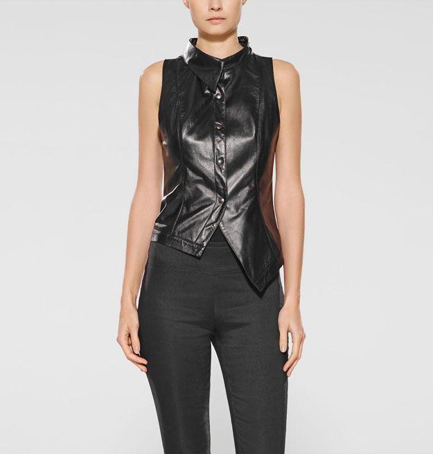 Creatieve hoeken. Verken nieuwe stijlhorizonten met dit zwarte asymmetrische jasje uit zacht leer. Draag dit mouwloze model als blouse, open met een basisstuk of boven een fijn gebreide trui. Werk af met uw favoriete broek of rok en een paar laarzen van Sarah Pacini voor een eigentijds silhouet.