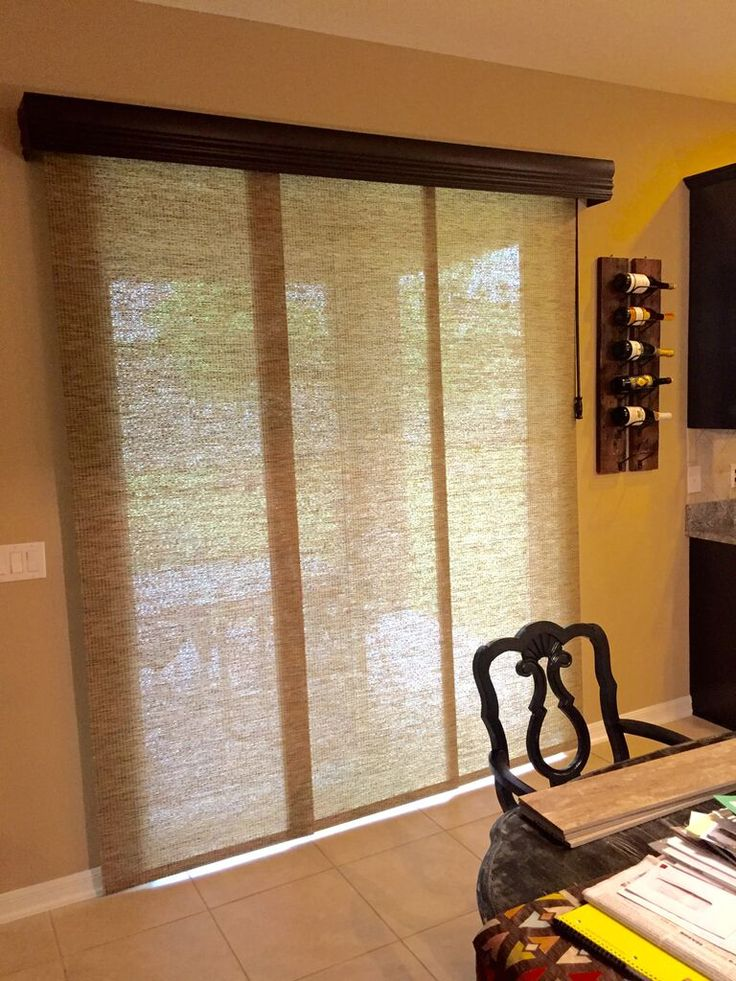 Sliding Panels are a great alternative to a vertical blind.   Cornice and wooden baton complete the look. Installation by Budget Blinds of Clermont