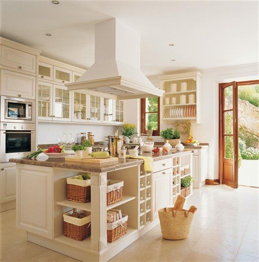 Love the glass cabinets and the corner section of the island with the baskets being used for storage of sorts.