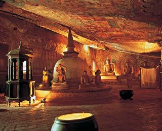 Dambulla Cave Temple  Sigiriya, Sri Lanka.  Hundreds of gilded Buddhist statues, some 50 feet long, sit, stand, and lie beneath 21,000 square feet of tapestry-like cave paintings depicting Buddha and his life. Statues of Ganesh and Vishnu are also garnished daily with fresh garlands from the pilgrims who come to worship.