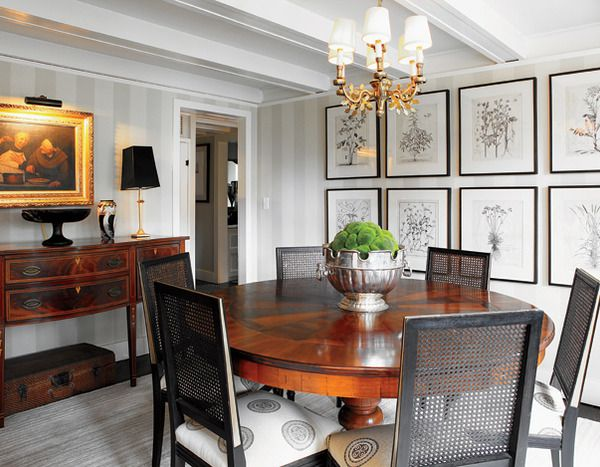 Striped wallpaper and botanical prints form an understated backdrop to a Regency sideboard and Biedermeier table in this charming dining room.