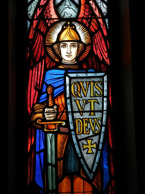 """St. Michael the Archangel - The second window depicts an Archangel, St. Michael. St. Michael is seen as the protector of the Church, and he led the heavenly army in the battle against the fallen angels. Michael's shield bears the inscription """"Quis ut Deus"""", which means """"Who is like God"""", a literal translation of Michael's name.    tjn"""