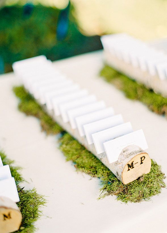 Take your rustic wedding up a notch, literally. For this escort card display notches were cut into wooden branches.