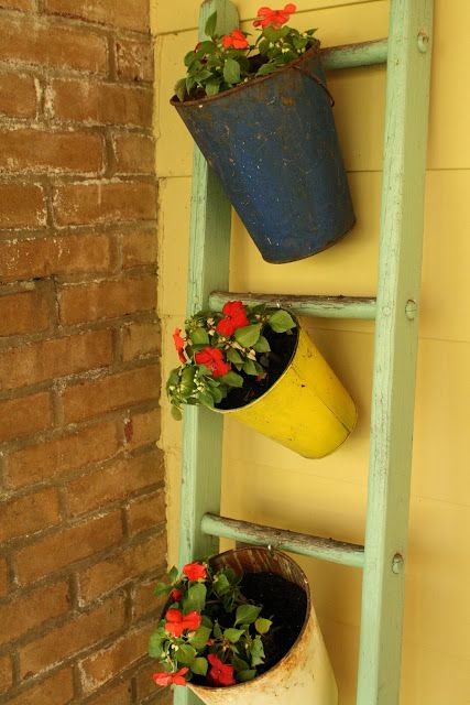 sap buckets on a ladder filled with plants- fabulous vintage porch idea!