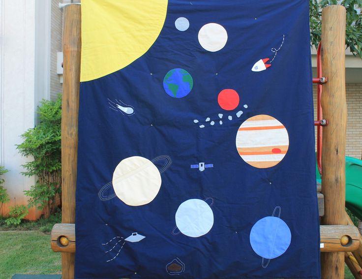"""Sonhar em ser um astronauta explorar o desconhecido, ver o nosso planeta """"de fora"""" e quem sabe encontrar um ET por ai? Desperte um (ou uma!) pequeno astronauta estando assim pertinho do Universo, do nosso sistema solar, com esse lindo edredom. <br> <br>Edredom exclusivo, 100% algodão, medidas aproximadas 1,15 x 1,30m, tamanho ideal para berço ou mini-cama."""