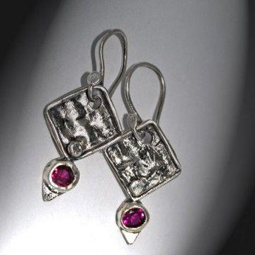 Kolczyki wykonane zostały od podstaw ręcznie, w srebrze  925 i 999. Rubinowe cyrkonie oprawione w fakturowane i oksydowane srebro.