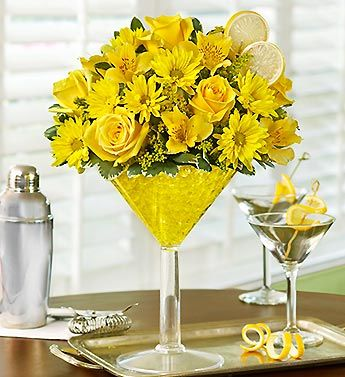 Send sunny sophistication with our truly original Happy Hour bouquet, inspired by the famous Lemon Drop Martini. Our floral version of the cosmopolitan cocktail is hand-crafted inside an oversized acrylic martini glass from cheerful yellow roses, daisies, alstroemeria and solidago. Topped with a faux lemon slice garnish, it's enough to fill anyone with sunshine and smiles.