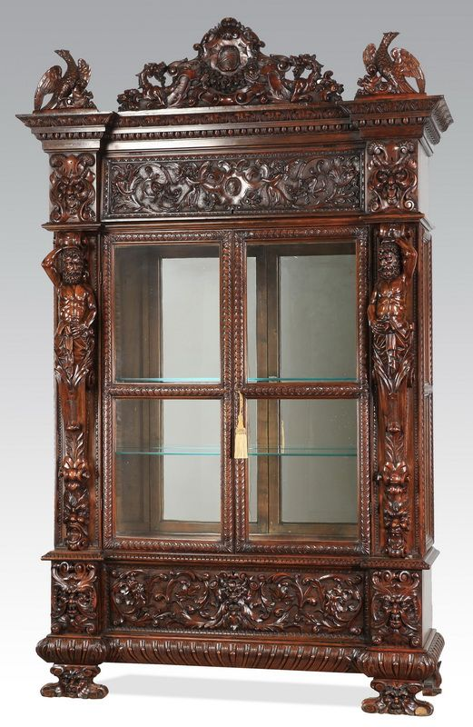 Renaissance Revival cabinet, late 19th century, the arched crest carved with a central shield cartouche with swags, surmounting the relief carved entablature of acanthus scrolls and green man masks, the doors opening to a mirrored back with two glass shelves, flanked by pilasters in the form of carved male term figures, the whole resting on carved feet of figural green man masks