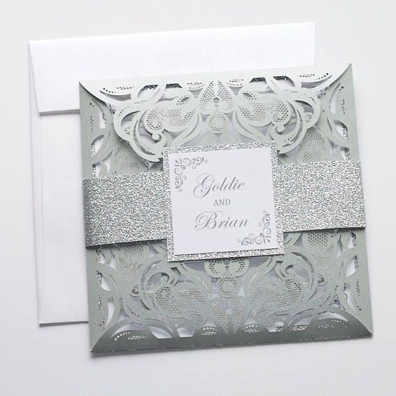 Elegant Laser Cut Wedding Invitation in Silver and White. Silver Metallic Ornate Laser Cut folder. Invitation printed on White metallic card stock with Silver glitter border. Silver Glitter Belly band with Front tag. RSVP Cards printed on White metallic. Outer and Reply envelopes