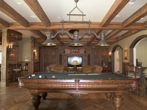 Antique Billiard Table with lovely carving and leather pockets in a room with a heavy, industrial looking three shade light above the table. Family room in the distance has large screen TV and comfortable seating, with kitchen pass through to the left with seating.