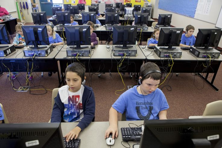 """The 7-year-olds in Natalie May's class have to stretch their fingers across the keyboards to reach """"ASDF"""" and """"JKL;"""" as they listen to the animated characters on their computer screens talk about """"hom..."""