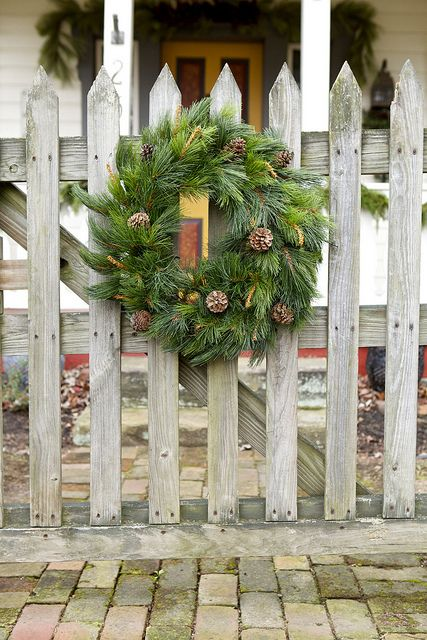 Green wreath on whitish fence.. love the pine cones. Reminds me of my wreath, minus the red bow. Maybe the wreath could stay on the fence past the holidays with just pinec ones?