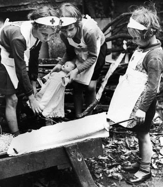 Children pretend to be nurses in the ruins of a bombed London, WWII. Courtesy of the BBC.