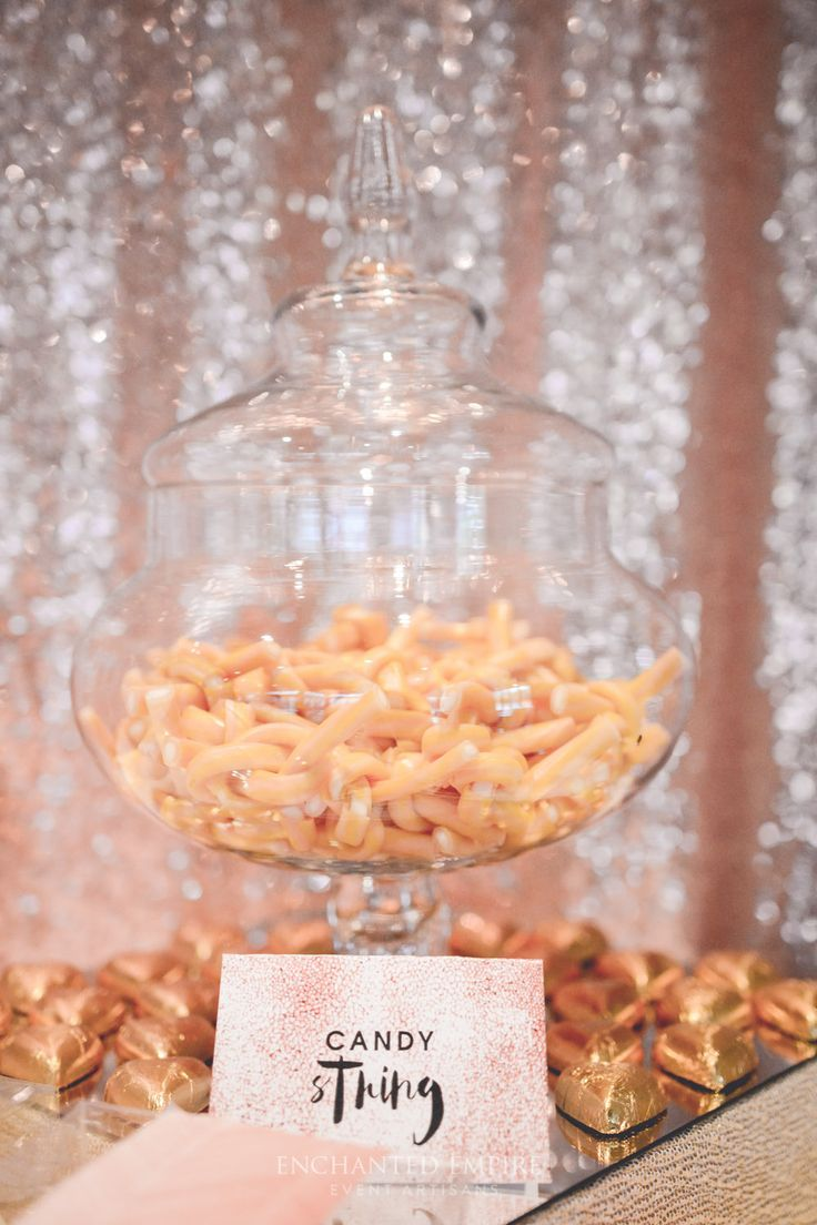 The warm shimmer of the copper sequined backdrop set the scene for this Copper & White Candy Bar. The contrast of crisp whites mixed with the warming tones of copper and gold, made for a visual treat. Deliciously decadent candy was packaged into individual portions so that guests could take a sweet treat away with them with ease.  Custom  graphics were used to carry through the theme with beautifully wrapped chocolates and individually designed candy labels.