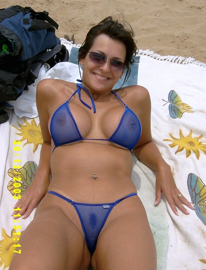 Tanned brunette milf in sunglasses and a sheer blue micro bikini pierced and proud