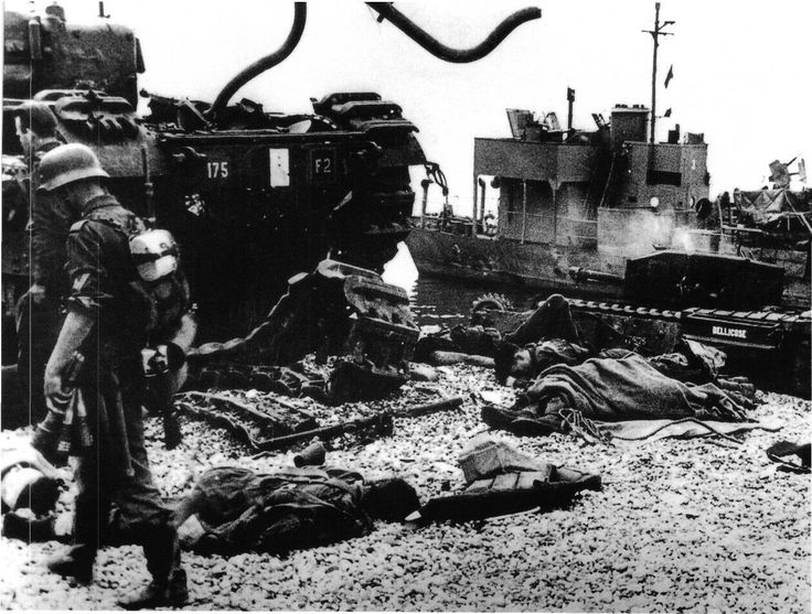 "German soldiers inspect the beaches littered with Allied casualties and equipment after the 19 August 1942 Dieppe Raid. The Churchill tank on the right is labelled ""BELLICOSE""."