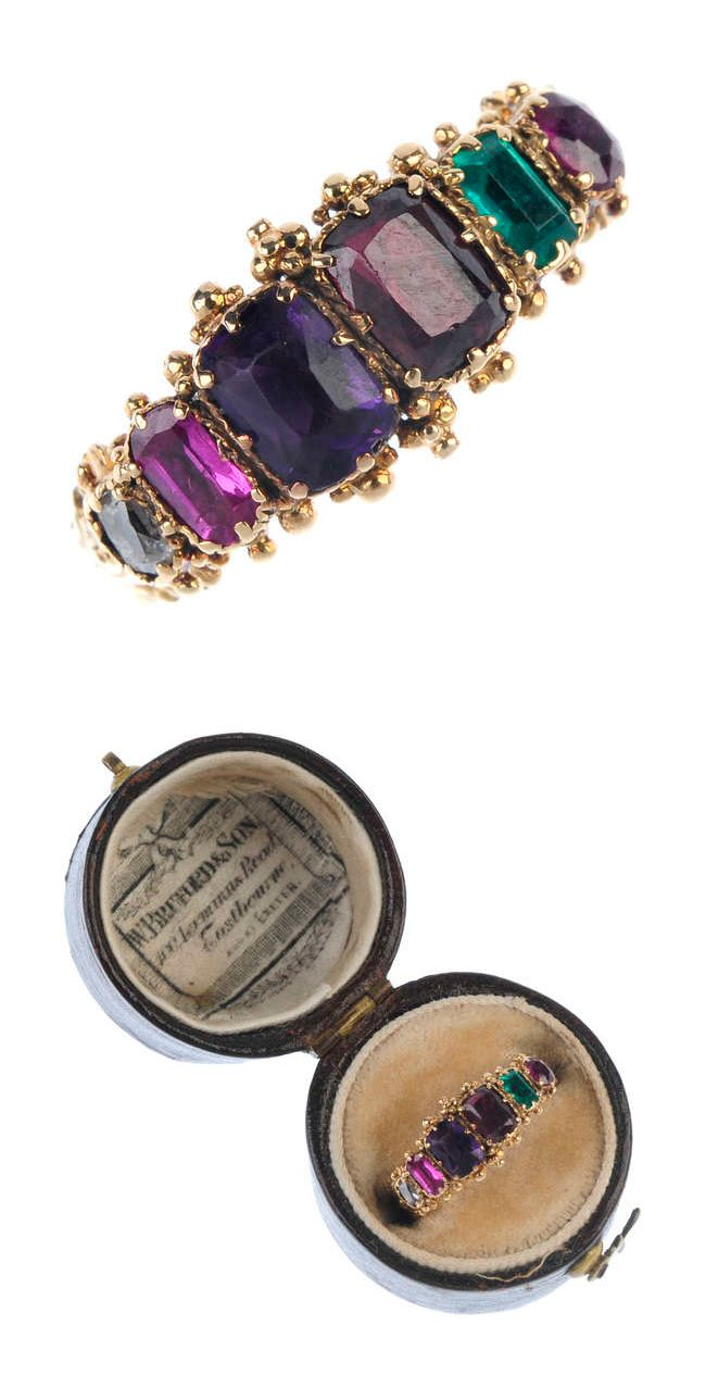 A mid 19th century gold 'Regard' ring. The graduated foil-back ruby, emerald, garnet, amethyst, ruby and diamond line, to the bead border and scrolling foliate band. Weight 2.3gms. With associated case.