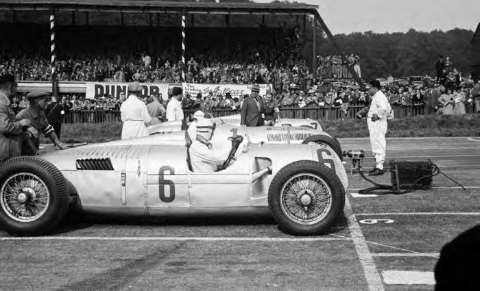 Donington GP October 2, 1937 – Three Auto Unions C-types and four Mercedes-Benz W125s made their way to Donington, persuaded to come by Fred Craner, who ran the circuit. This is the second row of the grid, and Rudolf Hasse is nearest the camera alongside Caracciola's Mercedes-Benz W125 with Hermann Müller in another Auto Union C-type on the far side. In between them is Dr. Karl Otto Feueriessen, the technical director of Auto Union.