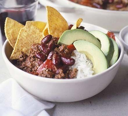 Chilli con carne in a bowl - with rice, tortillas, avocado, grated cheese, sour cream