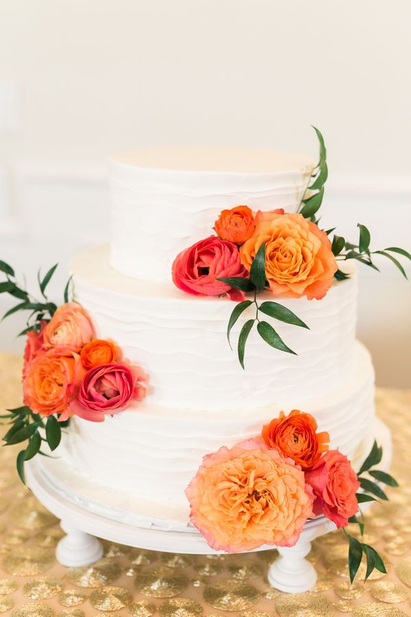 A buttercream wedding cake with cheerful pink and orange rose and ranuculus decorations for a fiesta wedding.