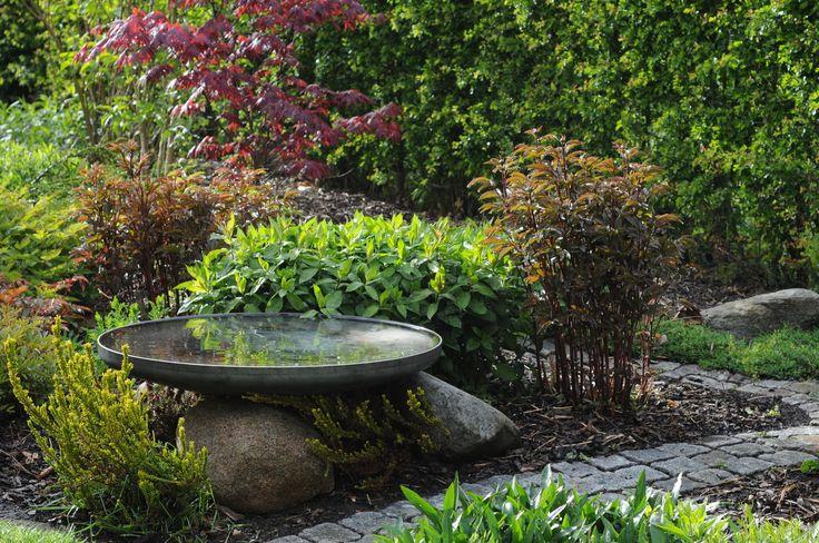 Rund spejlbassin smukt opsat på sten i haven