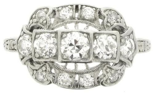 Diamond cluster ring, American, circa 1910. A platinum and iridium ring horizontally set with five round old cut diamonds in bead settings with an approximate total weight of 1.00 carats, surrounded by an openwork bezel set with eight round old cut diamonds in millegrain bead settings with an approximate total weight of 0.64 carats, above an openwork gallery, flanked by raised engraved shoulders, and with an approximate combined diamond weight of 1.64 carats. Berganza.