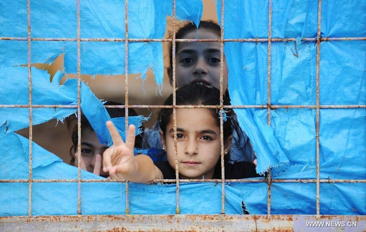 Syrian #refugee children look on from a tent at the Yayladagi refugee camp in Hatay province, Turkey, on Oct. 17, 2012. (Xinhua/Ma Yan)