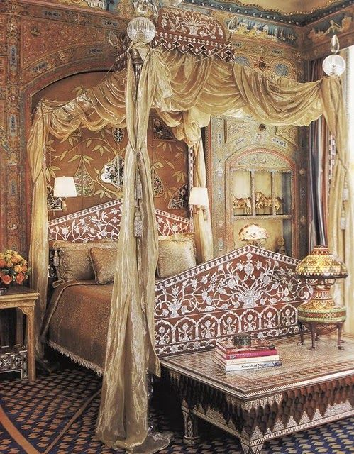 Blue and gold geometric rug, Anglo Indian inlaid bed and table, Mughal tree of life wall covering, swags of fabric in a romantic dream of a bedroom.