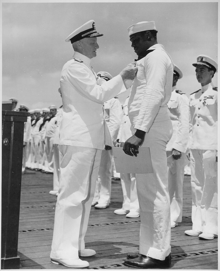 """""""Admiral C. W. Nimitz, CinCPac, pins Navy Cross on Doris Miller, at ceremony on board warship in Pearl Harbor, T. H."""", 5/27/1942. Miller was the first African-American to be awarded the Navy Cross."""