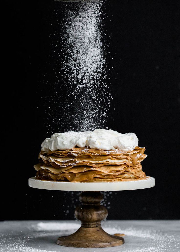 A crepe cake with layers of banana crepes and dulce de leche, topped with whipped cream and bananas foster!