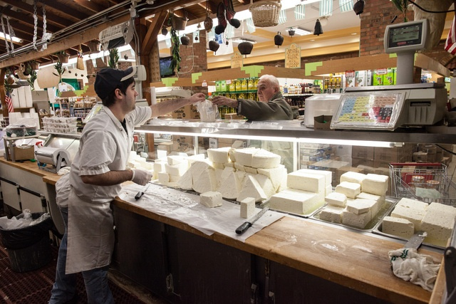 A cheese server helps a customer with his order of feta cheese at the Titan Foods supermarket in #Astoria, #Queens.