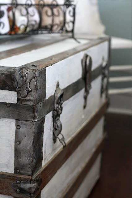 Sweet Old Trunks... one painted all white with bronze accents--done, just need to paint white. one all white with white wallpaper, and one (yet to find) white wiht bronze latches only. all 4 stacked, with canvas pillows on top, and another small crate on top.
