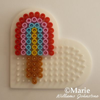 Cute mini rainbow color popsicle made with a heart shape peg board and fused Perler or Hama beads.