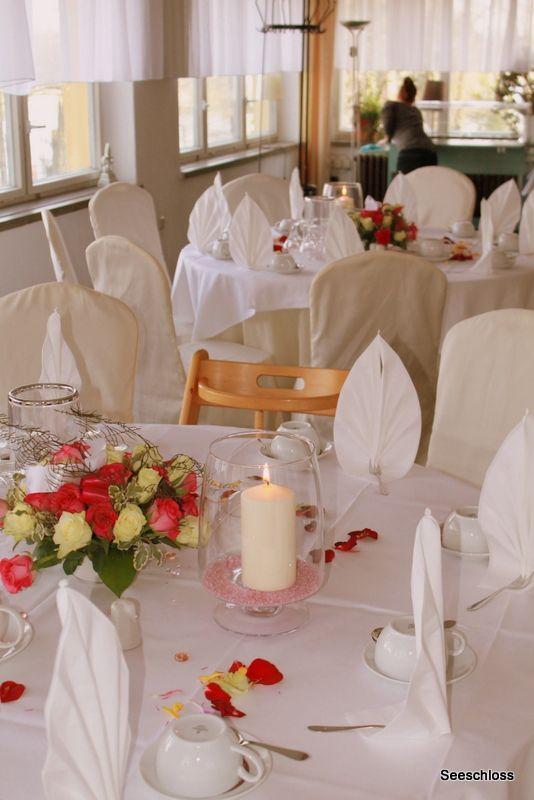 Runde Tische mit runden Blumengestecken im Seeschloss am Bötzsee .